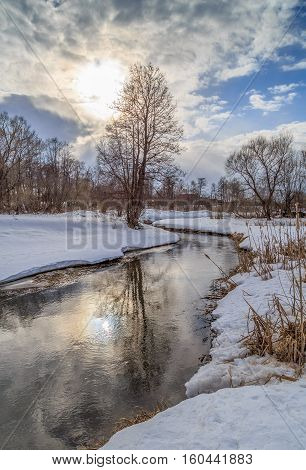 Winter landscape, river, snow, sun through the clouds, on the banks of alder