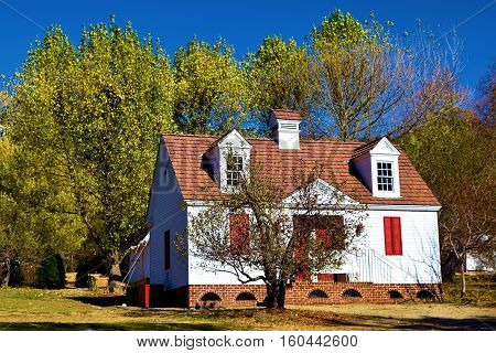 Deciduous trees changing colors during autumn foliage surrounding a colonial style house
