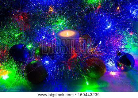 Photo by christmas night installation of candle christmas balls mandarins tinsel and garland.