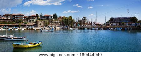 NESEBAR BULGARIA SEPTEMBER 06 2013: Fishing boats in the harbor of the old town of Nessebar Bulgaria. Old Nesebar is an ancient town on the Bulgarian Black Sea coast. Panoramic shot.