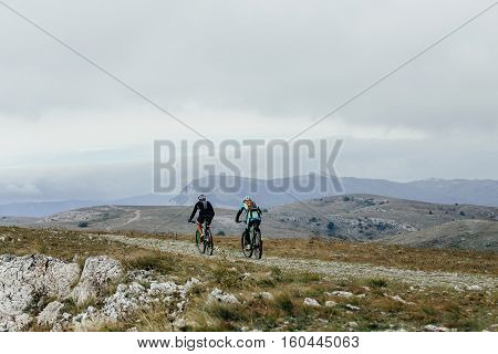 two athletes cyclists on mountenbike riding a mountain trail