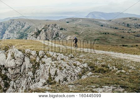 athlete cyclist on mountainbike rides on a mountain trail competitions in cross-country