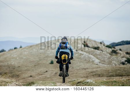 cyclist traveler with backpack on bicycle rides on a mountain trail