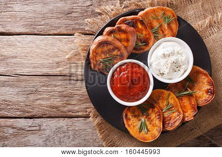 Grilled Sweet Potatoes With Rosemary Served With Sour Cream And Tomato Sauce Closeup On A Table. Hor
