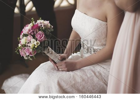 Beauty wedding bouquet in hands of the bride