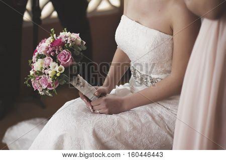 Beauty wedding bouquet in hands of the bride