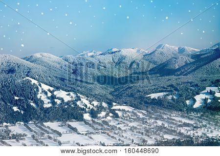 mountain valley with powder snow covered. winter background with snowflakes and copy space. new years or christmas card design