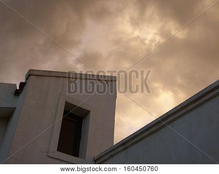 Una casa con cielo nublado de fondo