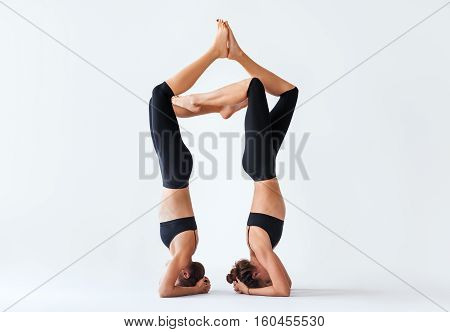 Two young women doing yoga asana supported headstand. Salamba Sirsasana