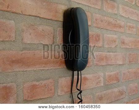 telefono fijo en una pared de ladrillo