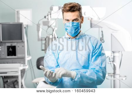 Surgeon wearing gloves in the operating room with surgical microscope on the background