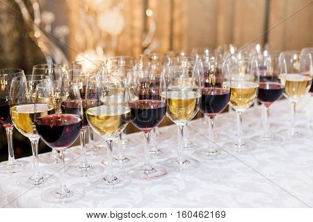 Many glasses with white and red wine on buffet table. Soft focus selective focus