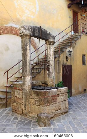 Medieval water well in San Quirico d'Orcia. Tuscany, Italy