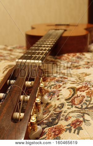 classical guitar with nylon strings on the bed