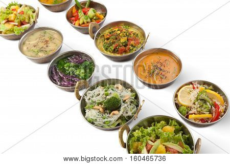 Vegan or vegetarian restaurant dishes, hot spicy indian soups, rice and salads in copper bowls. Traditional indian cuisine meal assortment isolated on white background. Healthy eastern local food