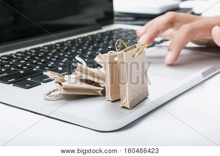 Online shopping concept. Miniature of reusable grocery bags and finger clicking the mouse pad.
