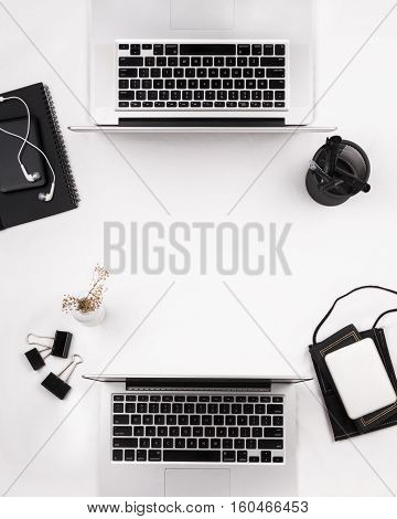 Flat lay of two laptops with stationeries and note book on a white table. Copy space.