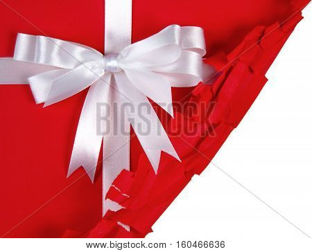 Partially unwrapped gift with a bow on top