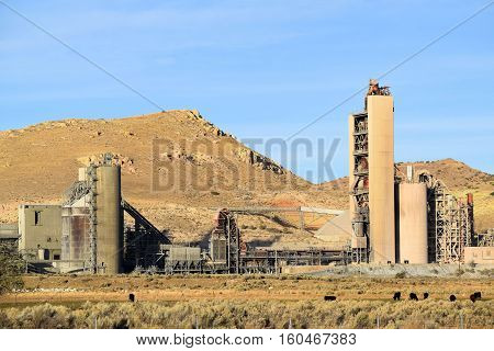 Industrial cement factory surrounded by a rural field with grasslands and sage plants