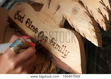 A Lebanese woman carving God bless our family on a wooden cedar shape in a Lebanese traditional craft shop. activity, Arabic, art, artistic, bless, brown, carving, craft,