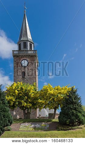 Inverness Scotland - June 1 2012: The tower of Old High Church along Bank Street and River Ness in Inverness against blue sky and on its green lawn with Laburnum trees. Black-and-white clock on brown stone tower.