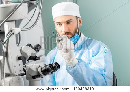Eye surgeon holding small surgical scissors for eye operation in the operating room near the microscope. Image with small deph of field focused on hands and scissors