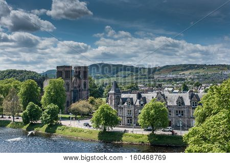 Inverness Scotland - June 1 2012: Brown stone Saint Andrews Cathedral is small in this wide shot of surrounding hills Ness River and other buildings. Shot off Castle Hill. Blue sky with white clouds