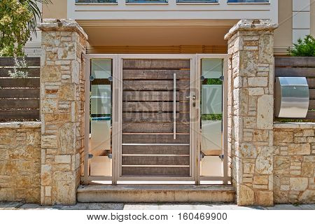 modern house entrance with metallic and wooden door