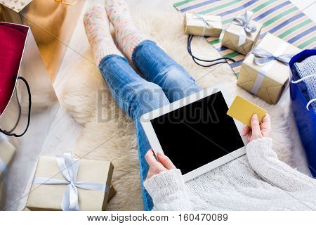 Christmas online shopping above view. Female buyer makes order at screen of tablet with credit card. Woman buys presents prepare to xmas eve, sits among gifts boxes and packages. Winter holidays sales