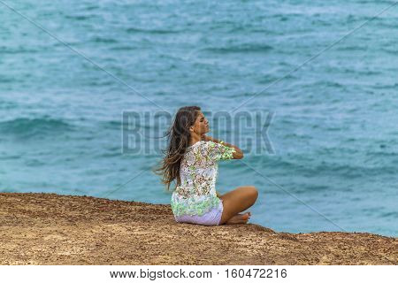 PIPA, BRAZIL, JANUARY - 2016 - Young attractive woman sitting at edge of rocky hill with the ocean at the background in Pipa Brazil