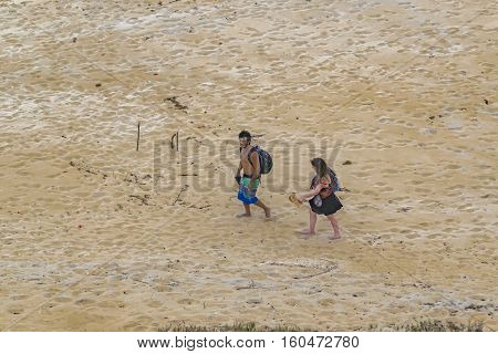 PIPA, BRAZIL, JANUARY - 2016 - Top view shot of young couple walking at empty beach in Pipa Brazil