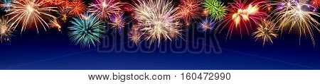 Lively multi-colored fireworks on dark blue background in panorama format ideal for New Year or other celebration events