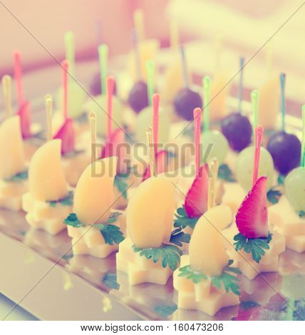 Canapes of cheese with fruits, close-up shot, toned image