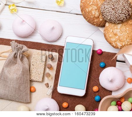 Template of smartphone among sweets on the table. Clipping path