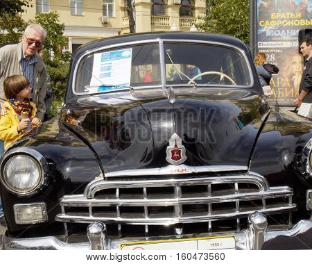 MOSCOW, RUSSIA - August 13, 2016: Senior adult man and elementary age boy with ice cream near soviet retro car full-size limousine of 1950s ZIM (GAZ-12). Festive occasion of the Moscow bus on the Frunze Embankment. August 13, 2016 in Moscow, Russia