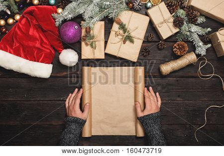 Male hand holding blank paper on dark wooden table with Christmas items. Christmas background