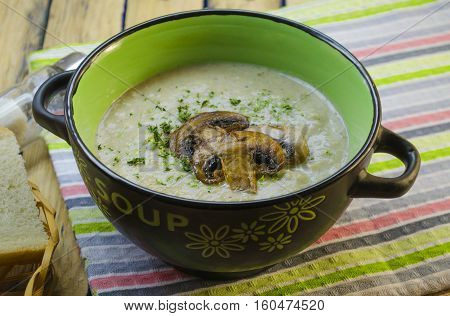mushroom cream soup in a tureen on a wooden table