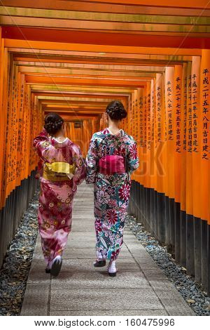 KYOTO, JAPAN - OCTOBER 8, 2016: Unidentified women at walkway in Fushimi Inari shrine in Kyoto Japan. This popular shrine have 32000 sub-shrines throughout Japan