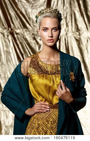 fashion studio photo of beautiful blonde woman with bright makeup wearing crown in hair yellow dress and green coat