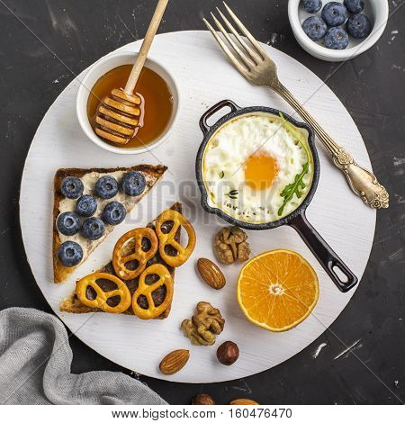Tasty modern breakfast. Fried eggs in a batch cast iron skillet and toast platter with peanut butter, blueberries, radishes and pretzels cookies on the board on a dark background. Top view