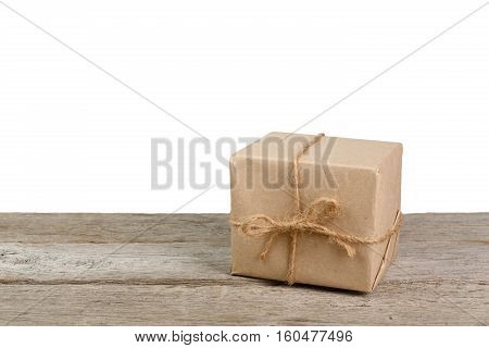 Gift box or mail parcel, post delivery wrapped with kraft paper and twine, lay on wood, isolated on white background. Craft present for winter holidays
