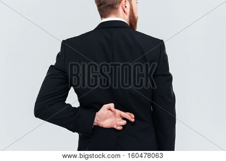 Cropped image of business man lying. Holding hand with fingers crossed behind his back. Isolated gray background