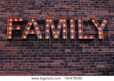 Lit Family Sign on Brick background. The illuminated sign appears nostalgic.
