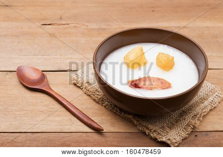 Traditional porridge rice gruel or congee in brown bowl with wooden spoon on wood table
