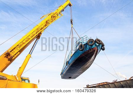 MOSCOW, RUSSIA - NOVEMBER 11, 2016: State Unitary Enterprise Mosvodostok performs recovery vessels on coastal winter parking. The ship hanging under the car boom crane.