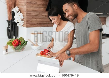 Picture of cheerful young couple cooking in the kitchen using tablet computer.
