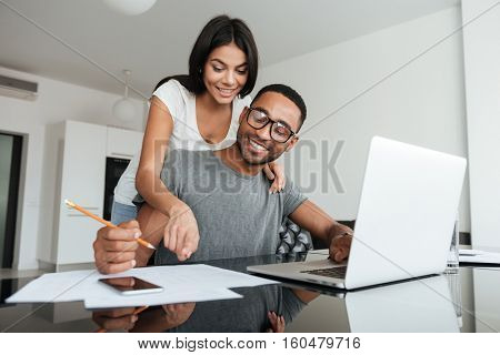 Loving young couple using laptop and analyzing their finances. Writing notes.