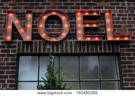 Noel sign on brick over window and Christmas tree.  Noel is the french word for Christmas.