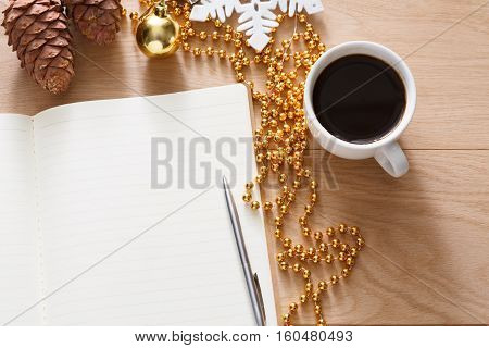 Christmas planning background. Prepare to winter holidays. Top view flat lay of xmas decorations, note papers, pen, coffee and mobile phone on wood. Copy space for wishlist or shedule