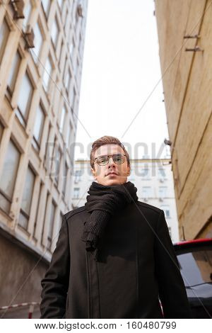 Vertical image of young business man in glasses and warm clothes standing on the street between houses. From below image